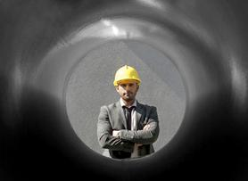 Man looking through pipe